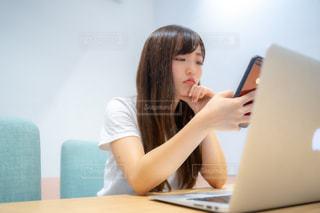 携帯電話をいじる女性の写真・画像素材[2397221]