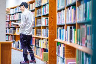 本棚の前に立っている男の写真・画像素材[2496081]