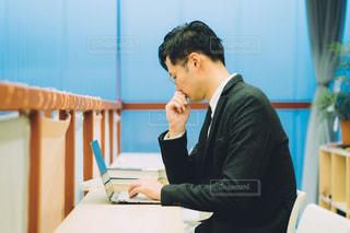 ノートパソコンを使ってテーブルに座っている男の写真・画像素材[2887316]