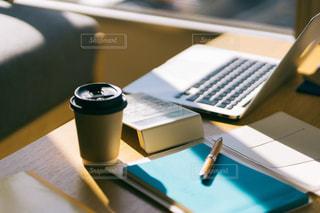 テーブルの上に座っているラップトップコンピュータ付きの机の写真・画像素材[2972275]
