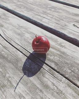 木のベンチに置かれた林檎の写真・画像素材[4418336]