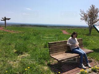 公園のベンチに座っている人の写真・画像素材[1251600]