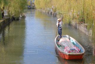 水の体の横に立っている人の写真・画像素材[1251638]