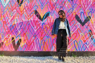 カラフルな壁の前に立っている人 - No.1002757