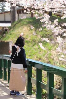フェンスの前に立っている人の写真・画像素材[1115980]