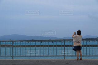 フェンスの横に立っている人の写真・画像素材[1119662]
