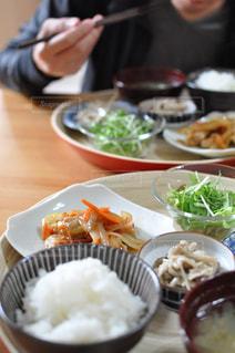 食品のプレートをテーブルに座っている人々 のグループの写真・画像素材[739198]