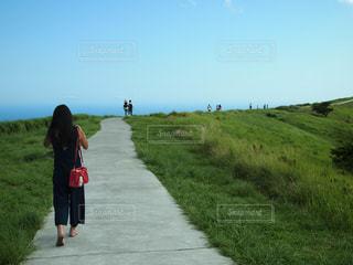 芝生の丘の上を歩く人の写真・画像素材[1017361]