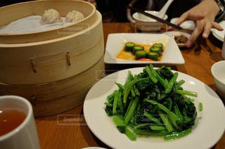 食品のプレートをテーブルに座っている女性の写真・画像素材[818330]
