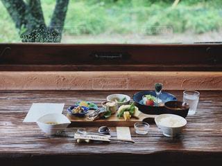 窓の横のテーブルの上の食べ物の皿の写真・画像素材[2286613]