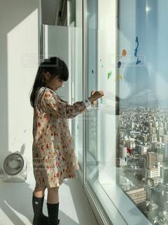 カメラに向かってポーズをとる鏡の前に立つ若い女の子の写真・画像素材[2377901]