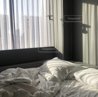 窓の横に座っている大きな白いベッドの写真・画像素材[2210906]