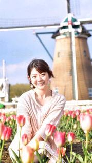 花の前に立っている人の写真・画像素材[1147998]