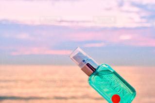 ビーチで水のボトルを保持している人 - No.1190563