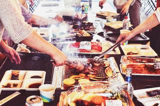 テーブルの上に食べ物を準備する人々 のグループの写真・画像素材[1203433]