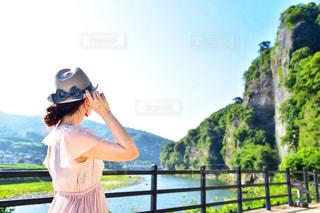 フェンスの前に立っている人の写真・画像素材[1261059]