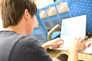 ラップトップ コンピューターを使用してテーブルに座っている男の人の写真・画像素材[1525558]