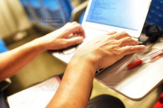 ラップトップ コンピューターを使用してテーブルに座っている人の写真・画像素材[1525560]