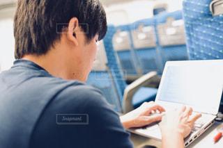 ラップトップ コンピューターを使用してテーブルに座っている男の人の写真・画像素材[1525561]