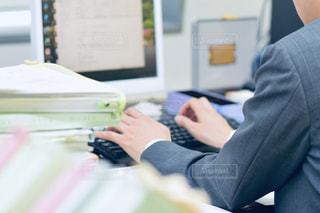 机に座って、ノート パソコンを使用しての人の写真・画像素材[1672014]