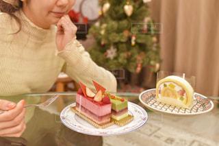 ケーキ前のテーブルに座っている女性の写真・画像素材[1685109]