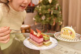 皿の上のケーキをテーブルに座っている女性の写真・画像素材[1685110]