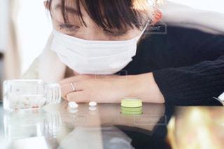 テーブルの上に座っている女性の写真・画像素材[1703035]