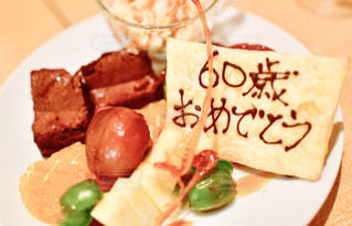 食べ物,スイーツ,ケーキ,文字,食事,屋内,デザート,テーブル,皿,チョコレート,料理,メッセージ,お祝い,記念日,手書き,還暦,日本語,還暦祝い,手書き文字