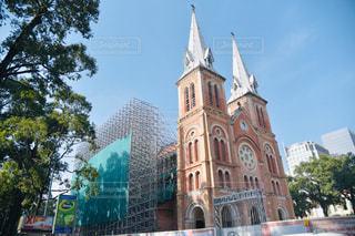 バック グラウンドでのサイゴン ノートルダム大聖堂と背の高い建物が付いている教会の写真・画像素材[1856594]