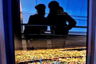窓の前でベンチに座っている人の写真・画像素材[1874886]