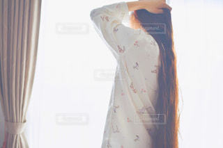 カーテンの前に立っている人の写真・画像素材[2211984]