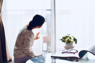 窓の前に立っている人の写真・画像素材[2211994]