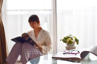 窓の横に立っている人の写真・画像素材[2211998]