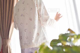 カーテンの前に立っている人の写真・画像素材[2212005]