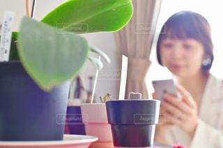 コーヒーを飲みながらテーブルに座る人の写真・画像素材[2212034]