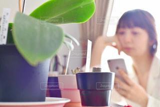 コーヒーを飲みながらテーブルに座っている女性の写真・画像素材[2212036]