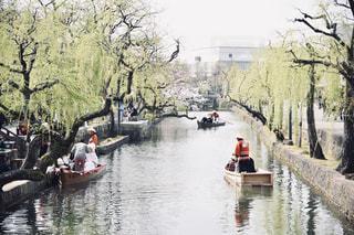 川のボートの後ろに乗る人々のグループの写真・画像素材[2280134]