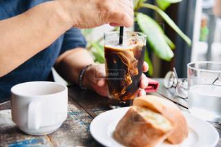 コーヒーを飲みながらテーブルに座っている人の写真・画像素材[2284915]