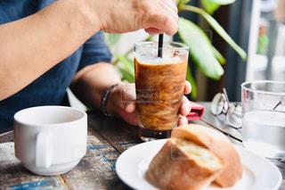 コーヒーを飲みながらテーブルに座っている人の写真・画像素材[2284916]