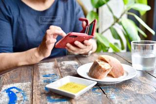 食べ物の皿を持ってテーブルに座っている人の写真・画像素材[2284929]