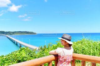 水域の隣のベンチに座っている人の写真・画像素材[2291134]