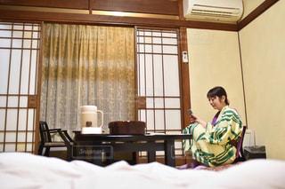 窓の隣のベッドに座っている人の写真・画像素材[2299823]