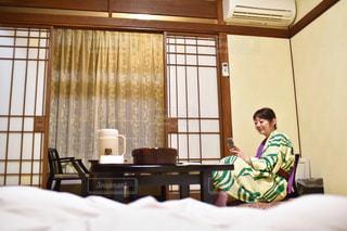 窓の隣のベッドに座っている人の写真・画像素材[2299824]