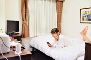 部屋のベッドに座っている人の写真・画像素材[2299829]