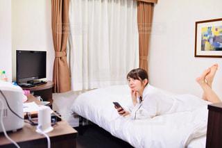部屋のベッドに座っている人の写真・画像素材[2299830]