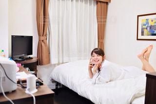 ホテルの部屋のベッドに座っている人の写真・画像素材[2299831]