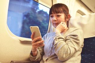 窓の隣に座っている若い男の子の写真・画像素材[2323876]