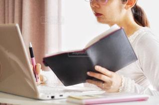 ノートパソコンを見てテーブルに座っている女性の写真・画像素材[2341922]
