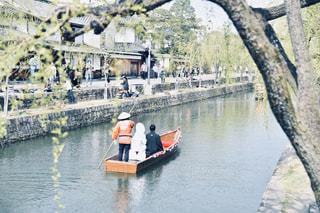 水の中でボートの後ろに乗っている男の写真・画像素材[2410269]