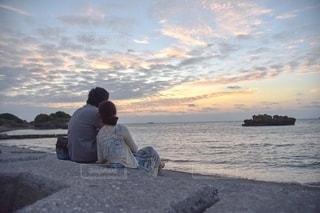 水域の近くのビーチに座っている男の写真・画像素材[2782910]